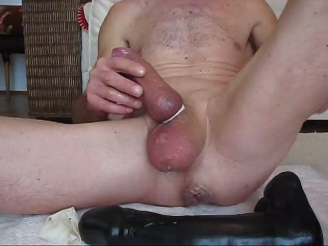 De zwarte dildo schuift diep in de homo anus