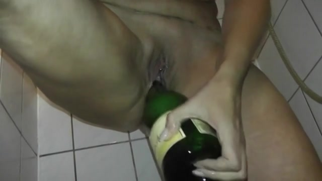 De fles spuit terwijl ze er mee mastubeerd