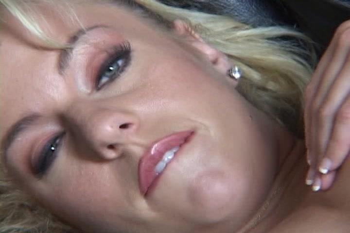 Kijkend in de camera mastubeerd ze haar kale kut