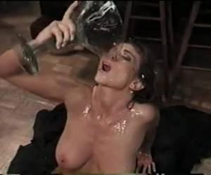 Met haar gezicht vol sperma drinkt ze na de gangbang het glas leeg